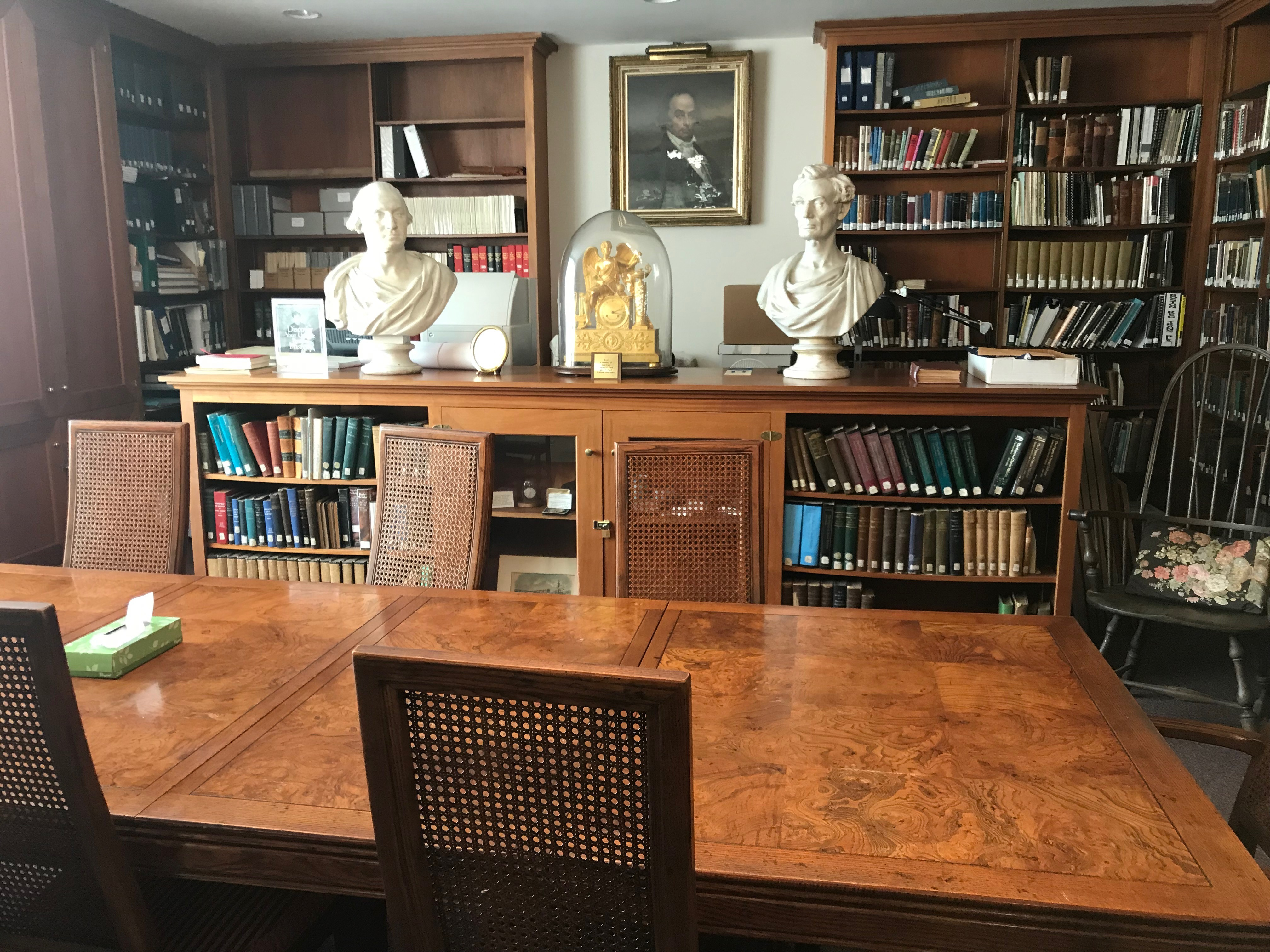 image of historical room with antique wooden furniture, busts of famous Massachusetts figures, and a gold clock