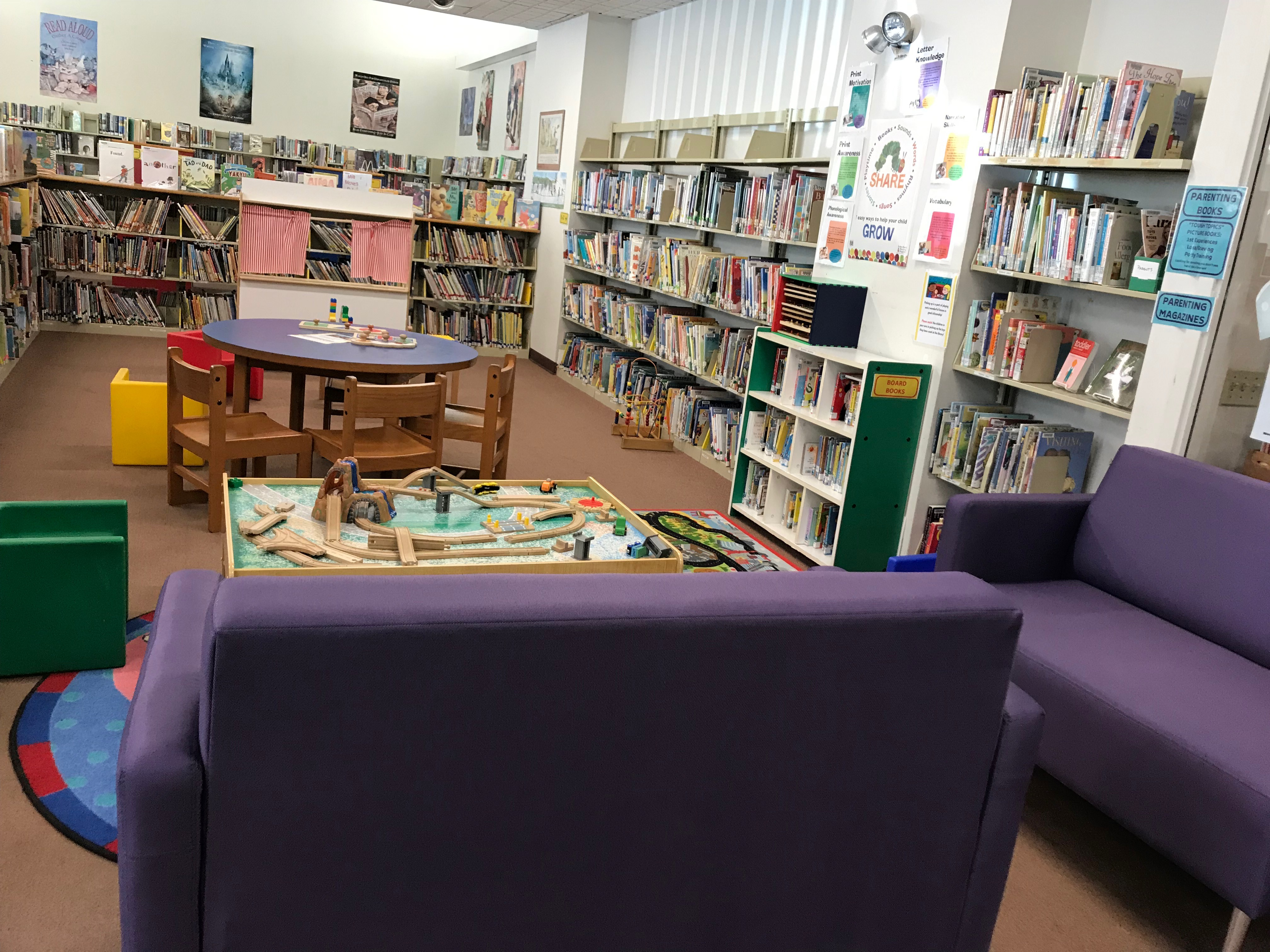 Image of the early literacy area of the children's room: purple couches, puppet theatre, train table, and many books.