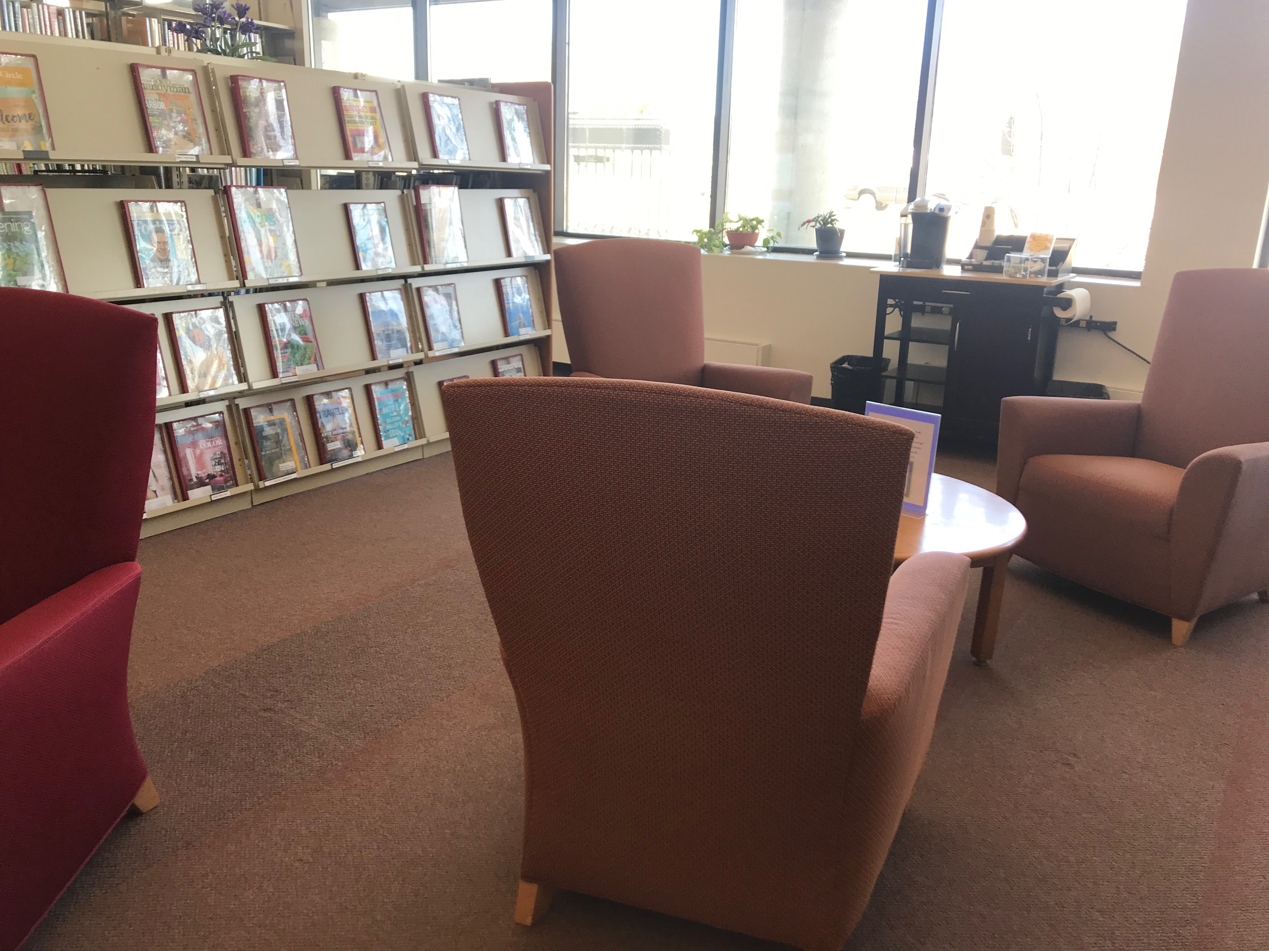 image of reading nook featuring armchairs, magazines, and keurig