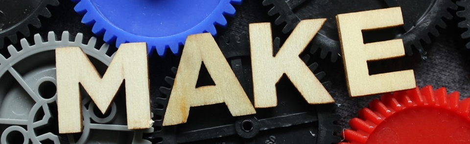 MAKE spelled out with wooded letters with multicolor gears in the background