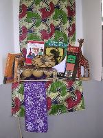 Photograph of red and green cloth, instruments and several books which are part of the Arts and Music of Africa and Asia Kit
