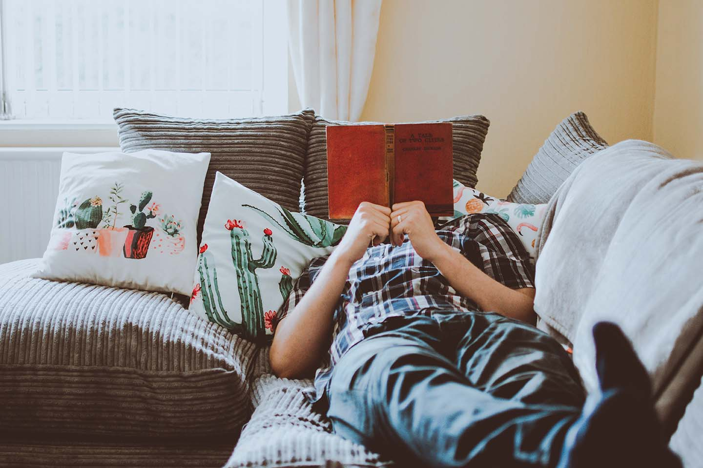 Man lying on a couch reading a book which obscures his face