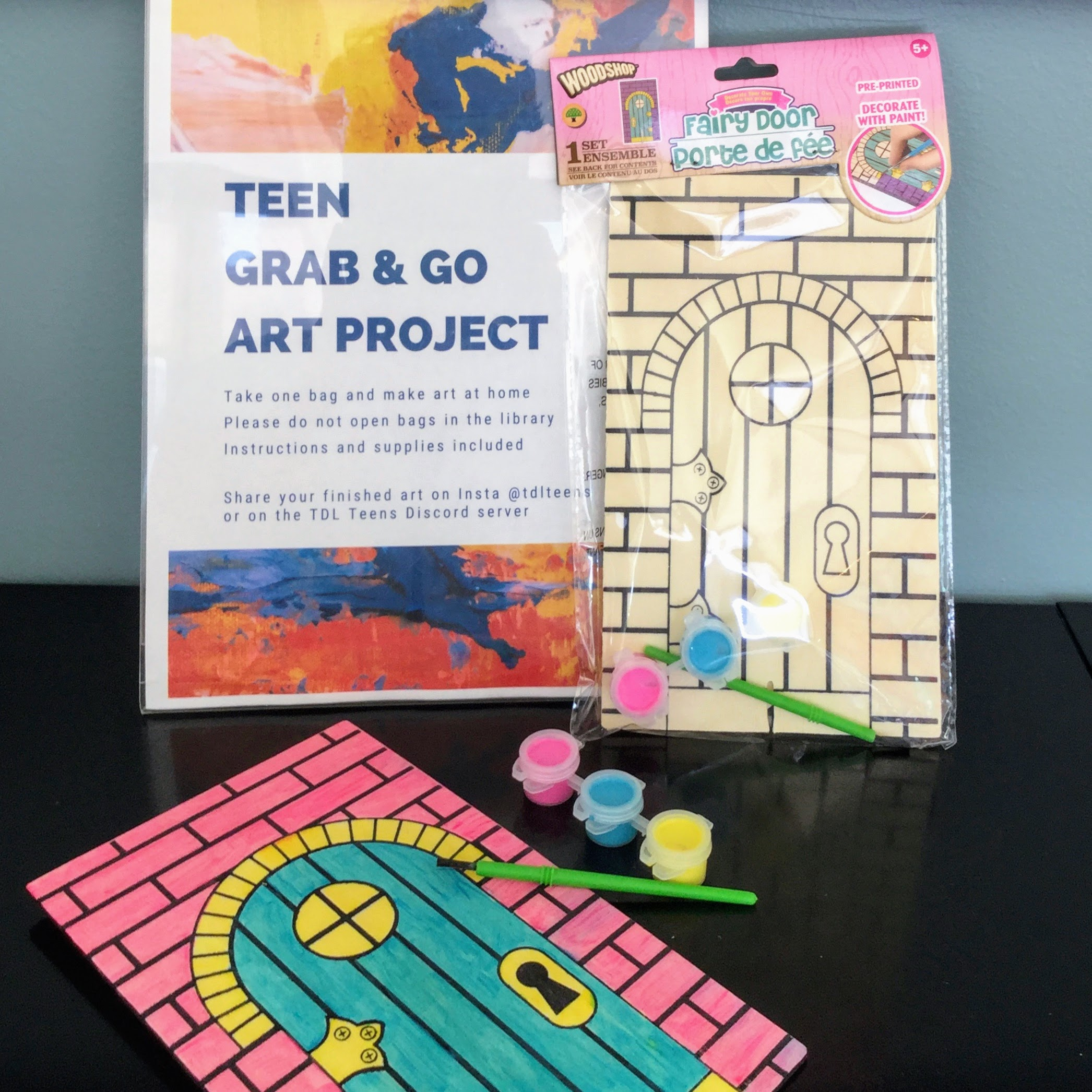 Photo of a fairy door kit, a painted fairy door, and a sign explaining teen grab & go projects