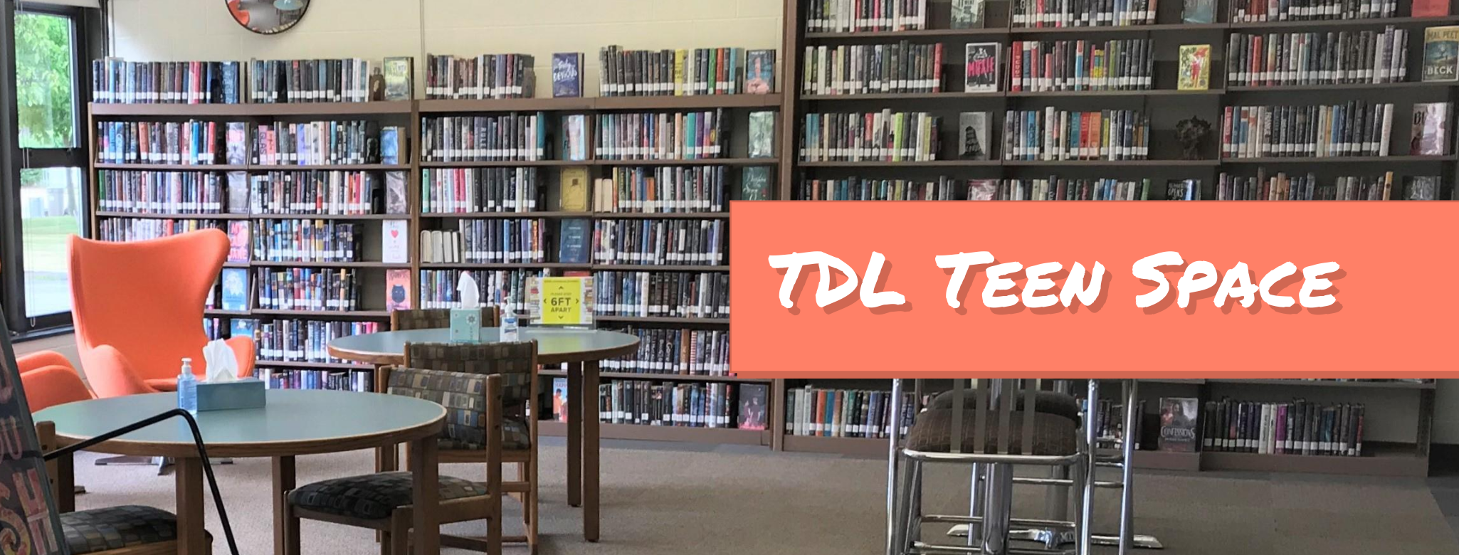 Photo of the bookshelves, chairs, and tables in the teen section with the text TDL Teen Space on an orange banner
