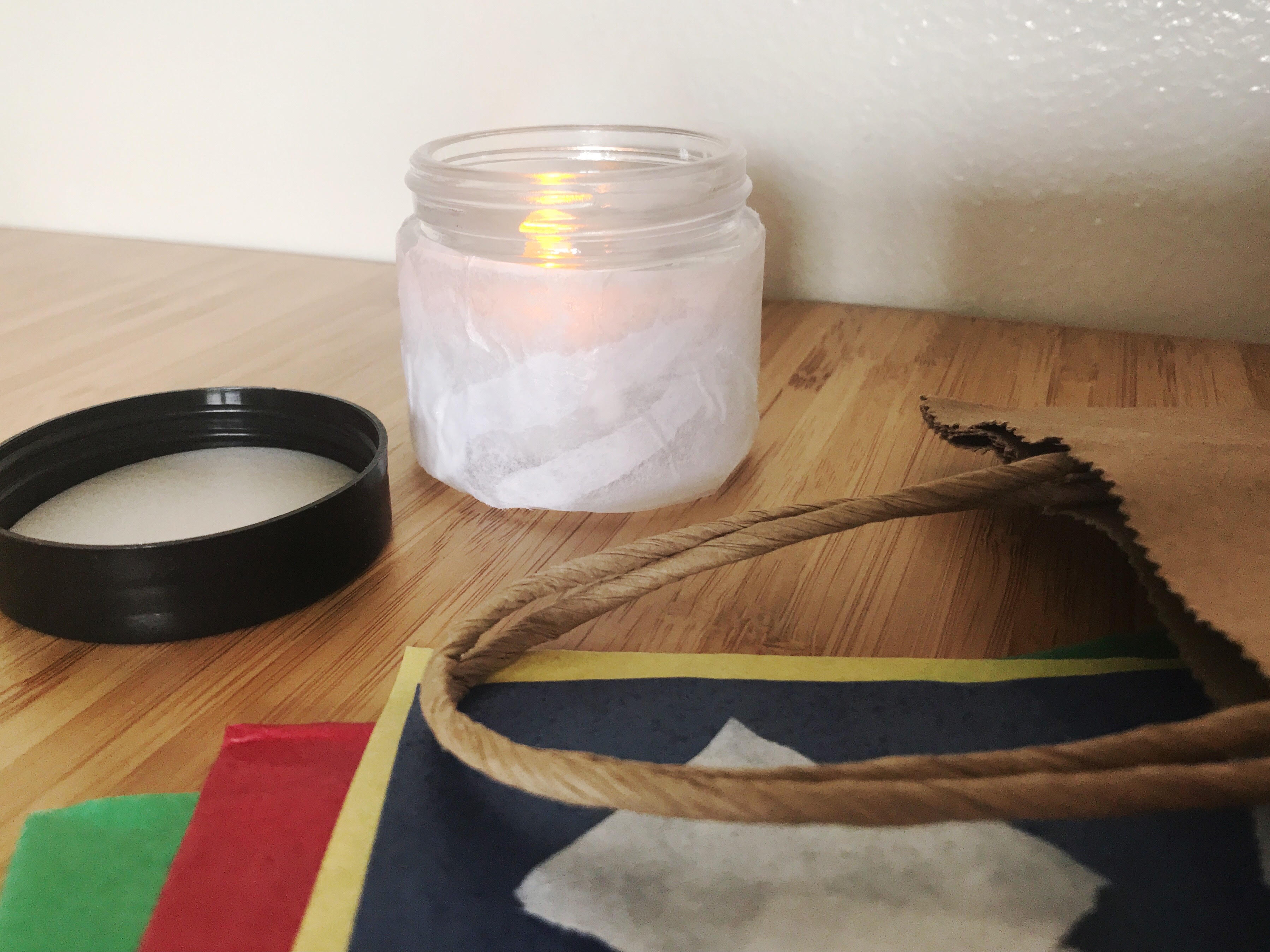 Photo of contents of grab and go kit: tissue paper, jar, battery operated candle