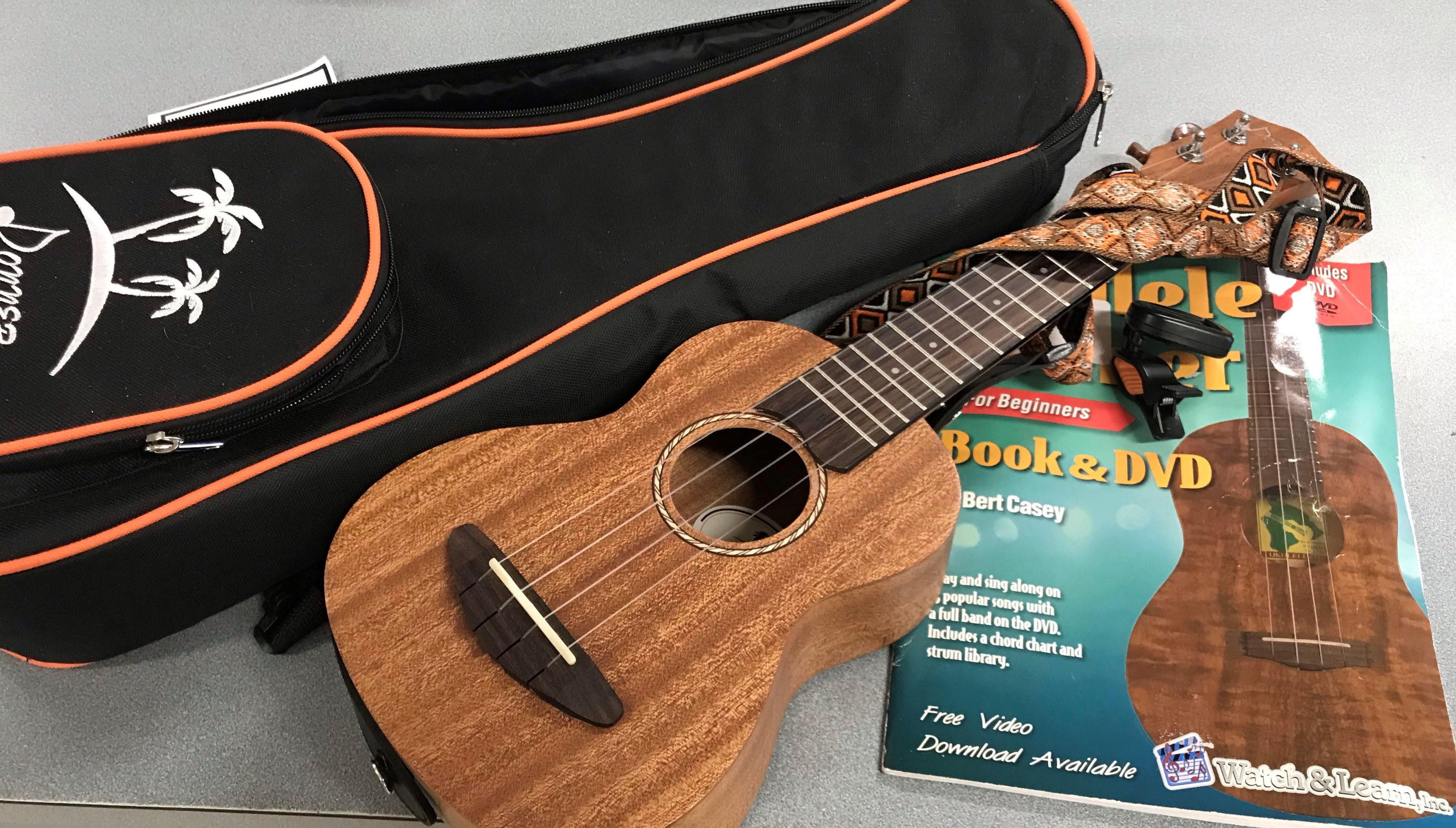 image of wooden ukulele with case, tuner, and songbook
