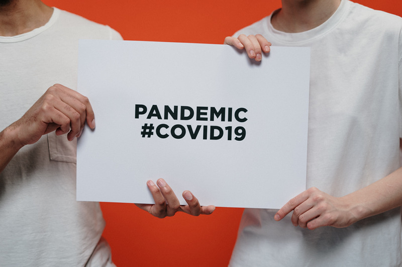 Two people holding a sign that says Pandemic #COVID19